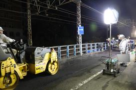 A battery light tower illuminates road maintenance work.